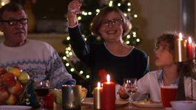 Happy elderly woman with family raises a glass at the Christmas table. Christmas decorations, candles on the table.  stock video footage