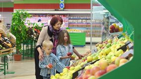Happy elderly woman with grandchildren in supermarket buys fruit. Portrait of grandmother of eighty years with her grandson and granddaughter in large modern stock video