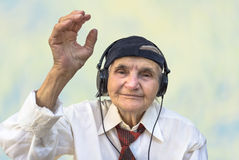 Happy elderly woman with headphones listening to music. Stock Photo