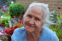 Happy elderly woman. In her flower garden Stock Images