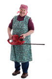 Happy elderly woman holding an electric garden saw. A lusty female senior with garden saw looks to viewer royalty free stock image