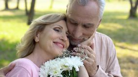 Happy elderly woman holding flowers, stroking male face, mature love, romance royalty free stock image