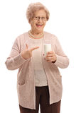Happy elderly woman holding a glass of milk and pointing Royalty Free Stock Photography