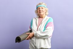 Happy elderly woman holding a yoga mat. Joyful old woman with mat is going to practice yoga exercises, dressed in white sports jacket and headband, isolated on royalty free stock images