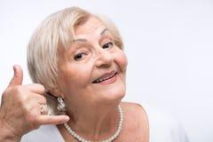 Happy elderly woman imitating a telephone call Stock Photos