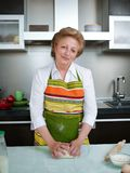 Happy elderly woman in the kitchen holding cooked dumplings and showing thumbs up. Royalty Free Stock Images