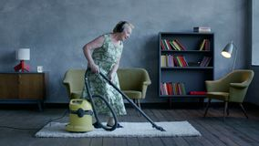 Happy elderly woman listening music on headphones and dancing with a vacuum cleaner, home fun stock footage
