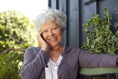Happy elderly woman making a phone call. Happy elderly woman sitting on a bench in backyard talking on mobile phone and smiling stock photos