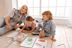 Happy elderly woman painting with her grandchildren stock images
