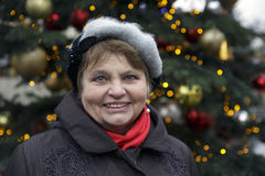 Happy elderly woman portrait outdoors in front of colourful winter lights. Happy elderly woman portrait outdoors Royalty Free Stock Images