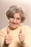 Happy elderly woman. Portrait of a happy elderly woman showing thumbs up Stock Photo