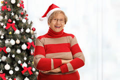 Happy elderly woman posing with her arms crossed in front of a C Royalty Free Stock Photos