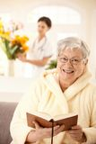 Happy elderly woman reading book. Portrait of happy elderly women sitting on couch, reading book, nurse arranging flowers in background stock images