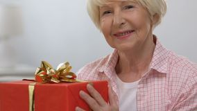 Happy elderly woman with red gift box smiling at camera, anniversary celebration. Stock footage stock footage