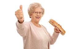 Happy elderly woman with sandwich making thumb up sign Royalty Free Stock Photos