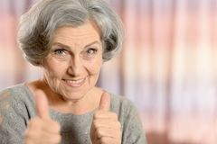 Happy elderly woman. Showing thumbs up isolated on color background Stock Photography