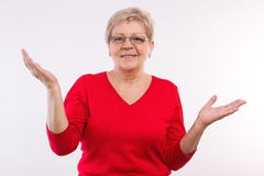 Happy elderly woman shrugging shoulders and throwing up her hands, emotions in old age. Happy smiling elderly senior woman throwing up her hands and shrugging Stock Image