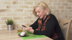 Happy elderly woman using a smart phone. Happy elderly woman sitting at a table and using a smart phone stock video footage