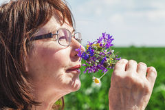 Happy elderly woman smelling bouquet of wildflowers Stock Photos