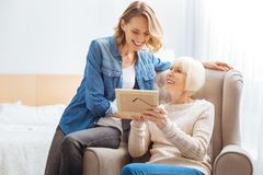 Happy elderly woman smiling while showing a photo to her granddaughter. Pleasant memories. Cheerful senior women feeling happy while sitting in a soft cozy royalty free stock photography