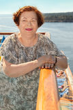 Happy elderly woman stands at board of ship Royalty Free Stock Image