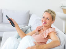 Happy elderly woman swapping the TV channels Stock Photos