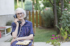 Happy elderly woman talking on the phone in the backyard Royalty Free Stock Image