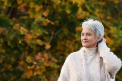 Happy elderly woman touchs her hair in nature. Happy senior woman enjoys a walk in autumnal nature stock images