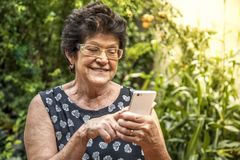 Happy elderly woman using cellphone royalty free stock photos