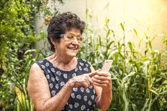 Happy elderly woman using cellphone royalty free stock images