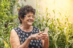 Happy elderly woman using cellphone stock image