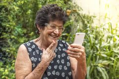 Happy elderly woman using cellphone royalty free stock photography