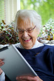 Happy Elderly woman using a tablet and laughing Royalty Free Stock Photos
