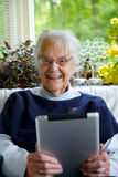 Happy Elderly woman using a tablet looking at the camera and laughing Royalty Free Stock Images