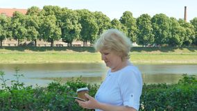 Happy elderly woman walks along the waterfront using smartphone and drinking coffee. Senior female walks along the. Waterfront using smartphone and drinking stock footage