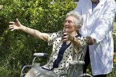Happy elderly woman in wheelchair with open arms Royalty Free Stock Photography