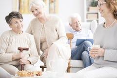Happy elderly women drinking tea. Happy elderly women having fun together while eating dessert and drinking tea Royalty Free Stock Image
