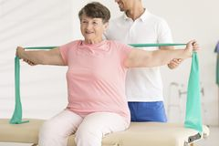 Elderly woman stretching during physiotherapy Stock Image