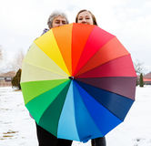 Happy elderly woman and young caregiver. Happy elderly women and young caregiver walking in the park with colorful umbrella Royalty Free Stock Photography