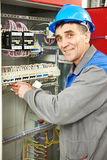 Happy electrician working at power line box stock photo