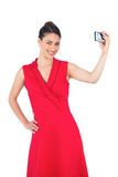 Happy elegant brunette in red dress taking picture Stock Images