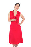 Happy elegant brunette in red dress texting Royalty Free Stock Images