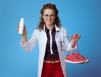 Doctor woman showing fitness sneakers and shoe deodorizer spray stock photos