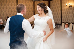 Happy elegant gorgeous married couple performing first dance wit. H heavy smoke in a stylish restaurant Stock Photos