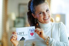 Happy elegant housewife showing gift certificate