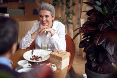 Happy elegant lady enjoying meeting in cafe. Enjoyable meetings. Waist up portrait of elegant happy smiling aged women looking with pleasure to her male friend royalty free stock photo