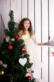 Happy elegant little girl decorating Christmas tree Royalty Free Stock Image