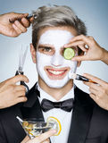 Happy elegant man with moisturizing facial mask. Surrounded by the multifunctional service (stylist, beautician, hairdresser). Photo of happy stylish man royalty free stock image