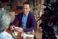 Happy elegant mature man have meeting in cafe. Enjoyable meetings. Waist up portrait of middle aged elegant happy smiling male sitting in cafe with cup of coffee stock photos