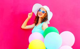Happy elegant woman with an air colorful balloons is having fun. On a pink background Stock Photos